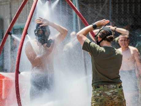 An Australian Army soldier directs a member from Indonesian Army through the decontamination shower during the Chemical Biological Radiological Nuclear (CBRN) training activity at the Regiment's out training facility in October 2017. Picture: Department of Defence