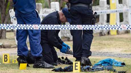 Police forensics officers examine the officers' gun at the scheme. Picture: Julian Andrews
