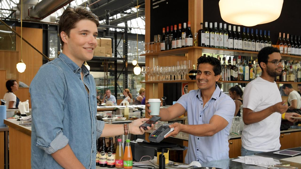 Daniel Vassilev orders a coffee from Sydney cafe Garson's manager Sam Sardana with his neo bank account. Picture: Tracey Nearmy.