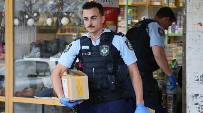 Police raid a store at Bankstown City Plaza in 2018 after police seized more than $200,000 cash and 4000 tins of baby formula. Picture: David Swift