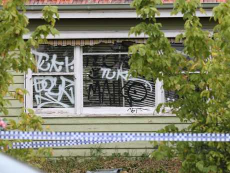 Police tape outside the graffiti-scrawled house at Bundoora where the accused had been living before his arrest. Picture: David Caird.