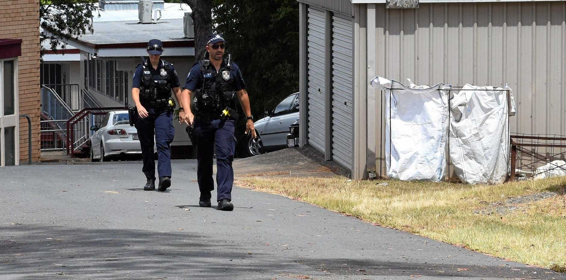 Gympie Police search the grounds of nearby schools for any clues or evidence.