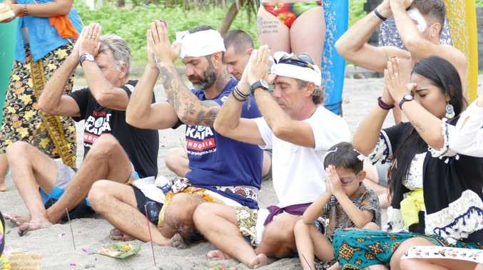 Damien Rider (purple shirt) prepares for a paddle-out in Bali to honour victims of child abuse and suicide.