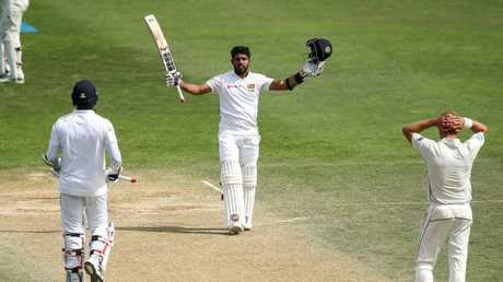 Kusal Mendis celebrates his 6th Test century with Angelo Mathews while Neil Wagner of New Zealand looks on.