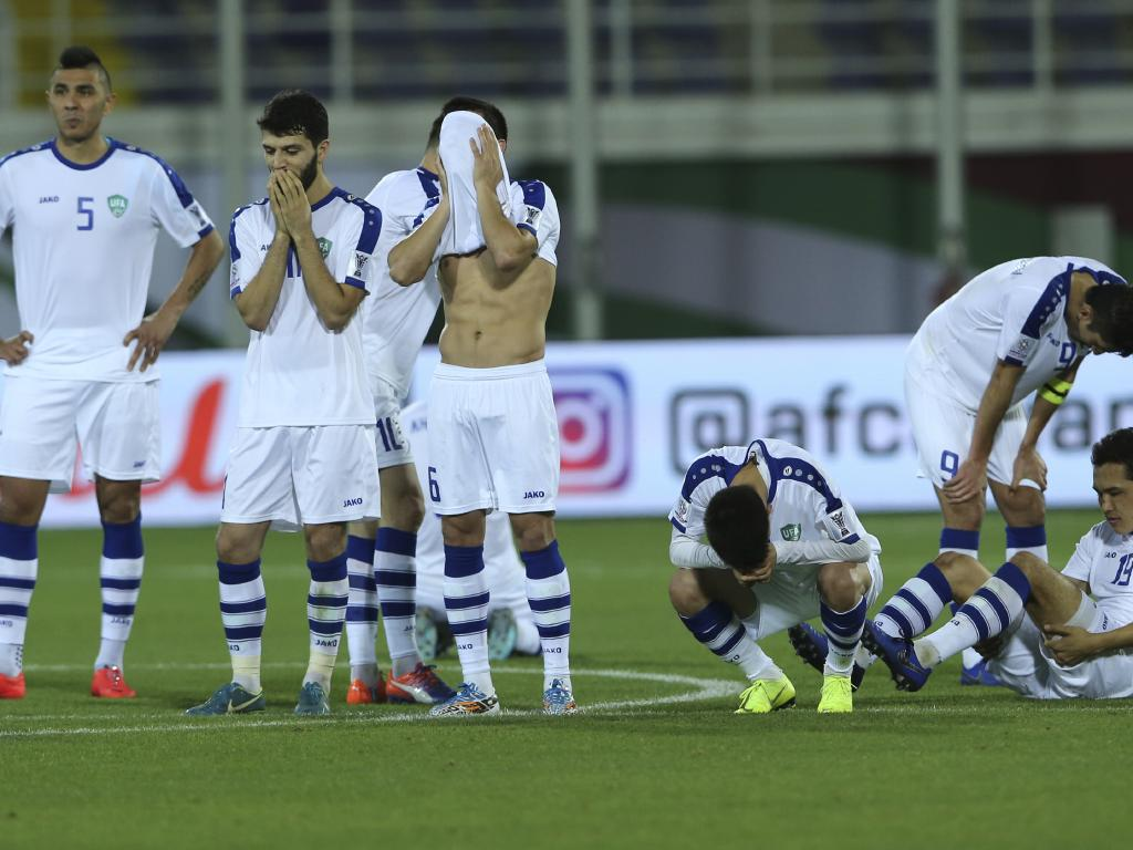 Uzbekistan players show their disappointment after their defeat at the hands of Australia.
