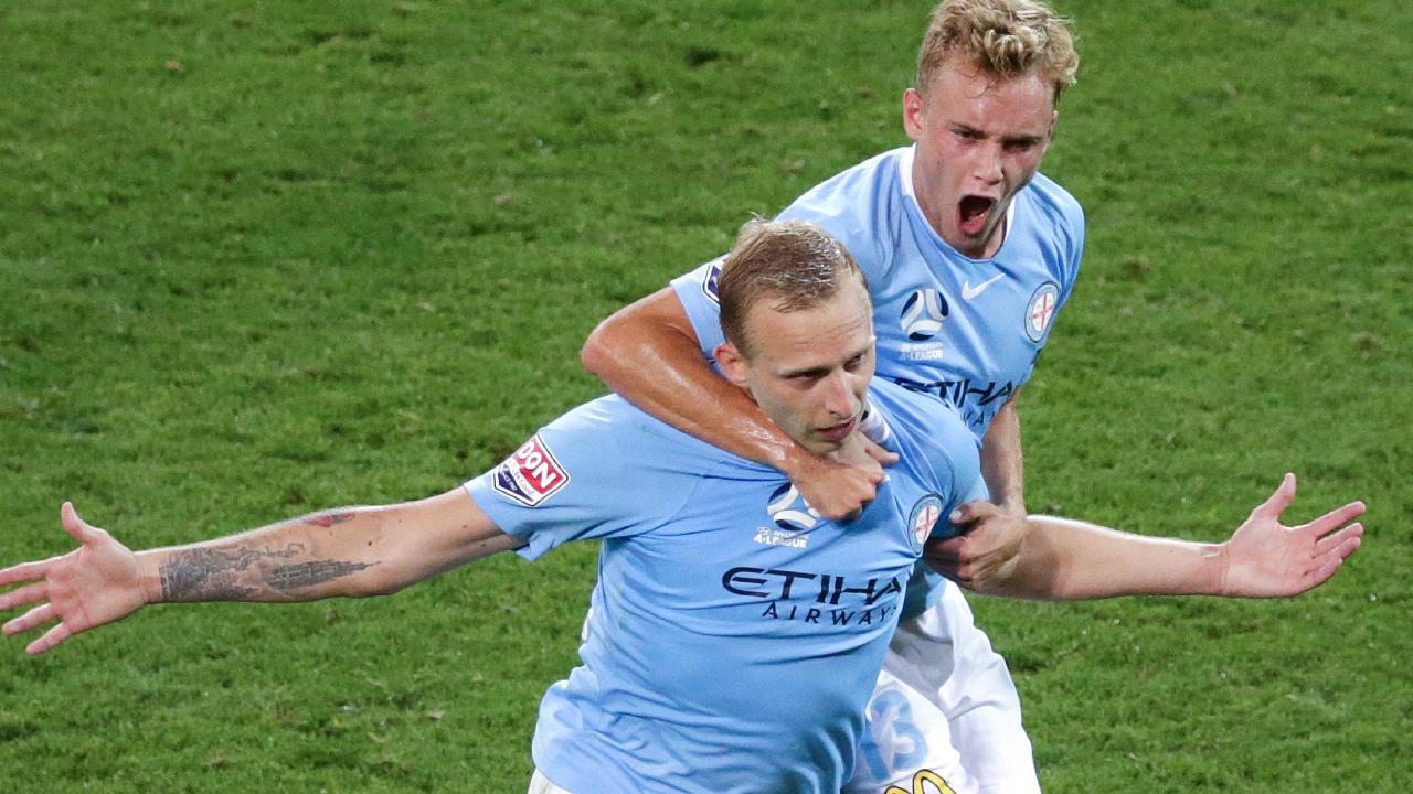 Nathaniel Atkinson jumps onto goalscorer Ritchie de Laet. (AAP Image/George Salpigtidis)