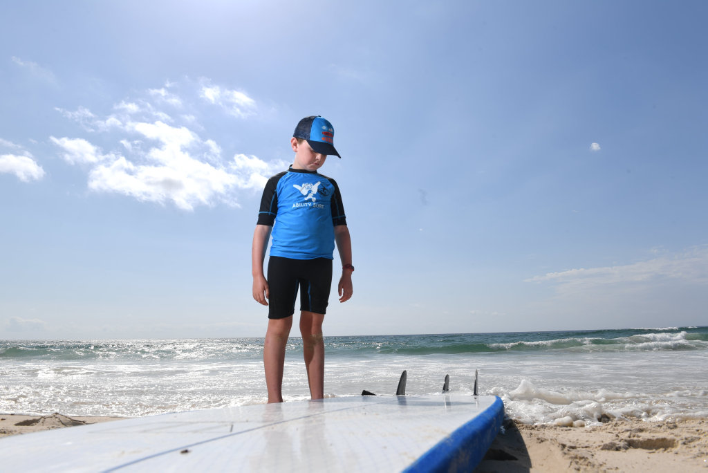 Image for sale: Ability Surf coach Emma Bracken works with Logan Paisley, 8, of Goonellabah on their latest surf lesson at Lighthouse Beach in Ballina.