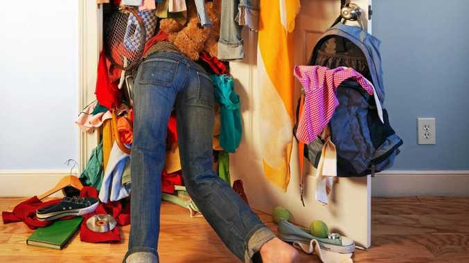 MESSY BUSINESS: A woman, not the author, diving into her very messy, unorganized closet, similar to the author's, looking for something to wear.