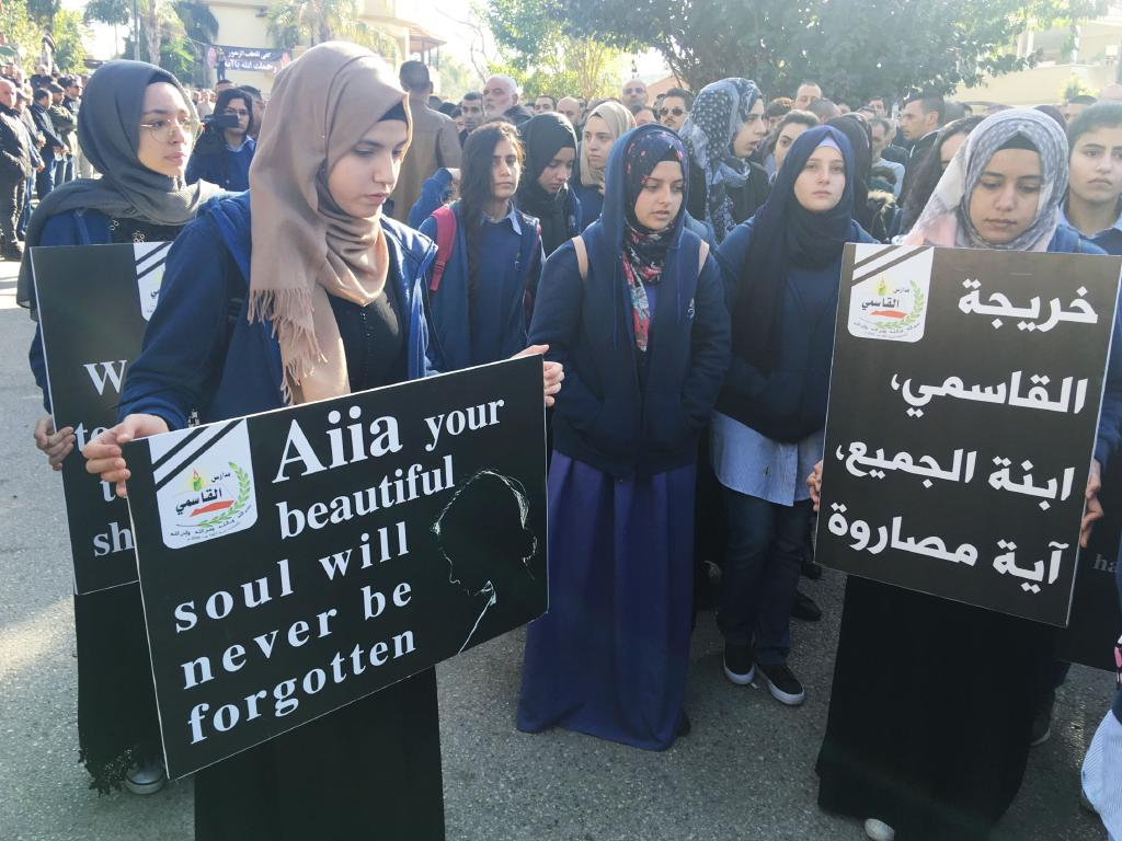 Mourner hold signs as Aiia's coffin arrives in her home town.  Picture: Ella Pellegrini