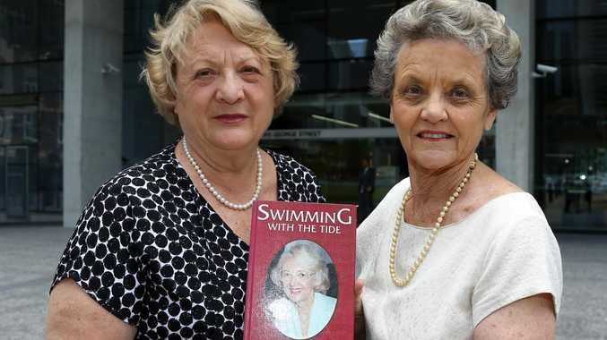 Sisters Pamela Godsall Smith and Janice Drake with a picture of their mother Joan Godsall and her book. Picture: AAPImage/David Clark