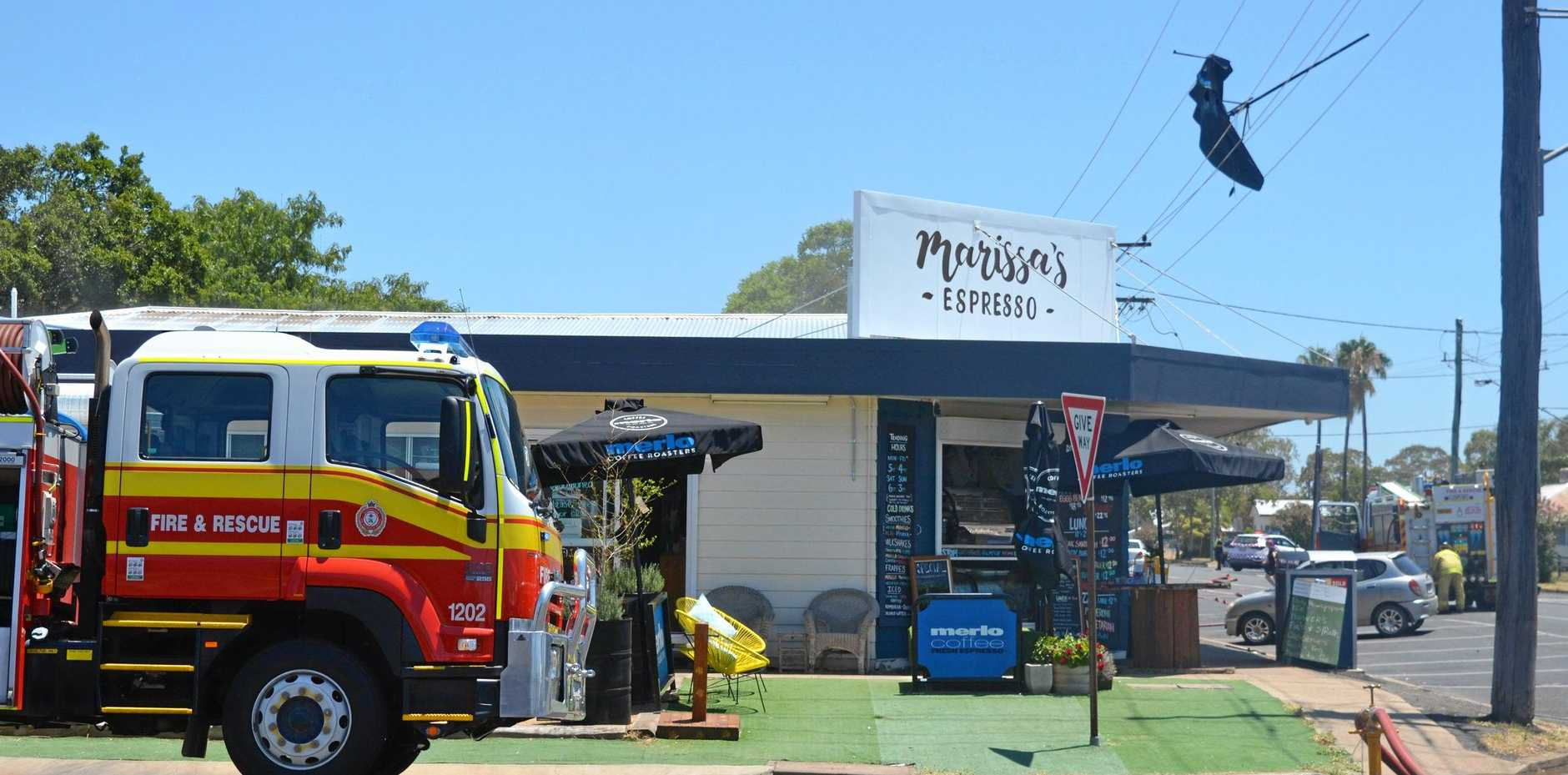 FREAK FIRE: An umbrella flew up into powerlines cutting power to surrounding traffic lights and causing a fire above the bottle shop.