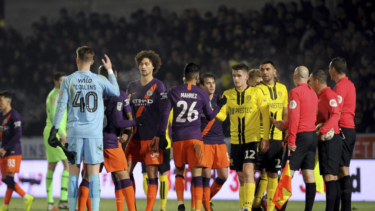 Burton and Manchester City players shake hands after the English League Cup semifinal