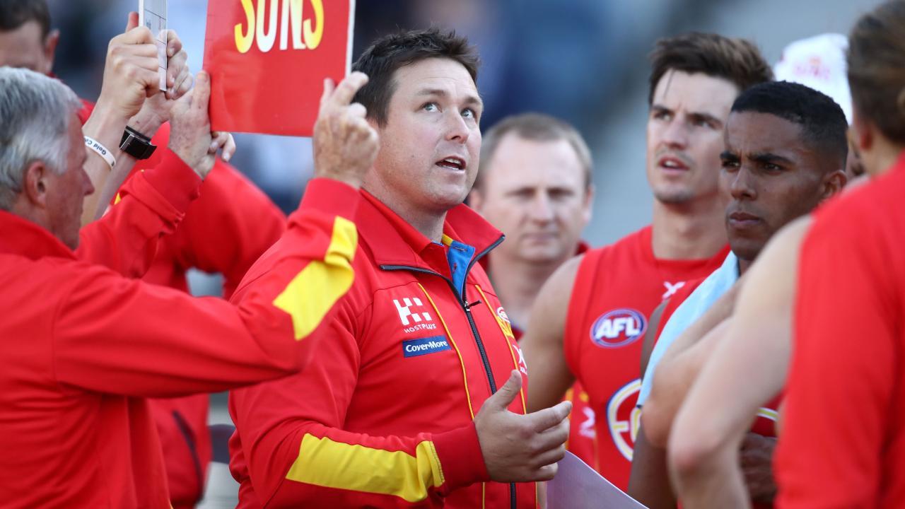 Gold Coast coach Stuart Dew talks to his players.