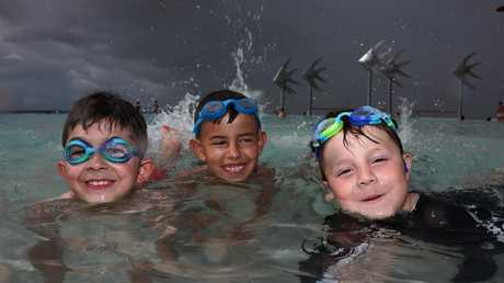 Christian Te with Cruz and Christian Ponze enjoy the water of the Cairns lagoon as storms approach from the south east. Picture: PETER CARRUTHERS