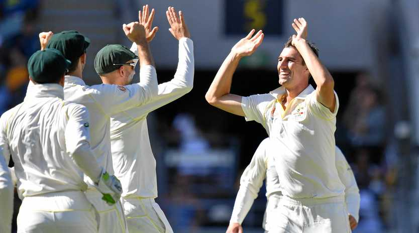 Pat Cummins (right) celebrates with teammates after getting the wicket of Sri Lanka's Lahiru Thirimanne. Picture: Darren England/AAP
