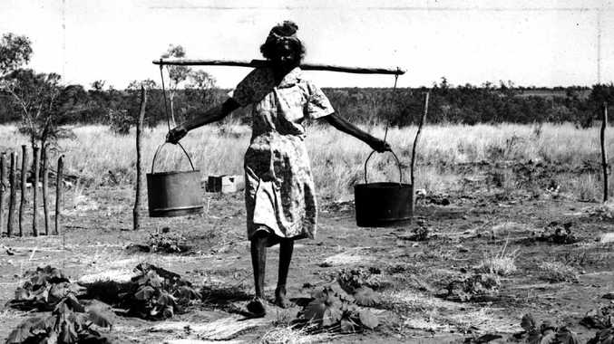 A Gurindji woman carrying water at the Wattie Creek settlement circa 1970. Picture: Northern Territory Photographic Services
