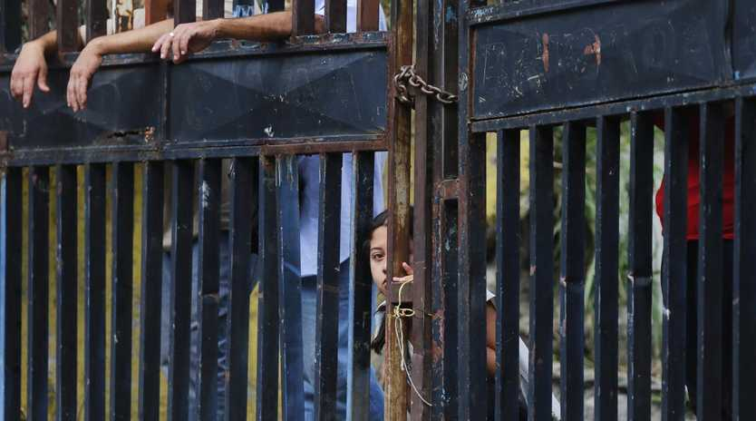 Residents watch anti-government protesters clash with security forces in Caracas, Venezuela on Monday. Picture: Fernando Llano