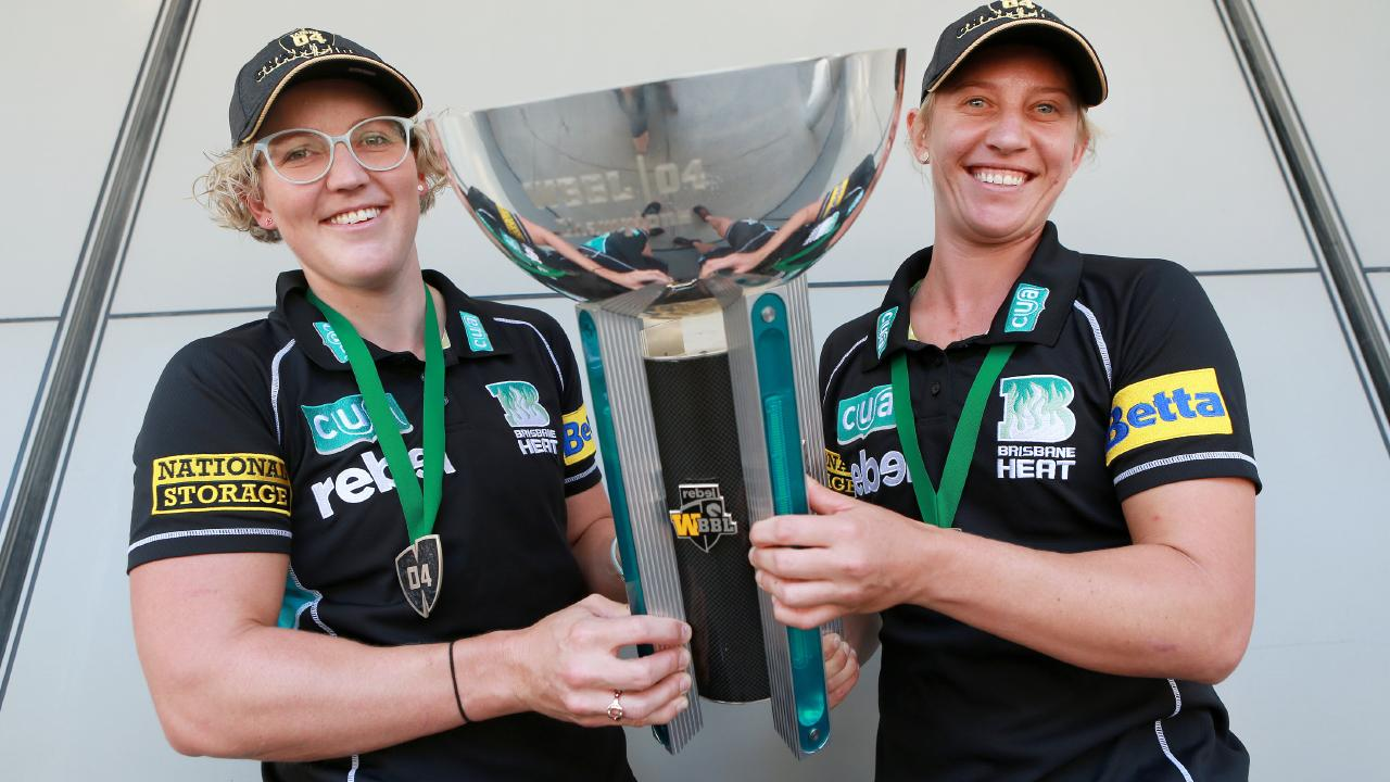 Brisbane Heat players Laura Harris (left) and Melissa Kimmince with the WBBL winning trophy at Brisbane Airport.