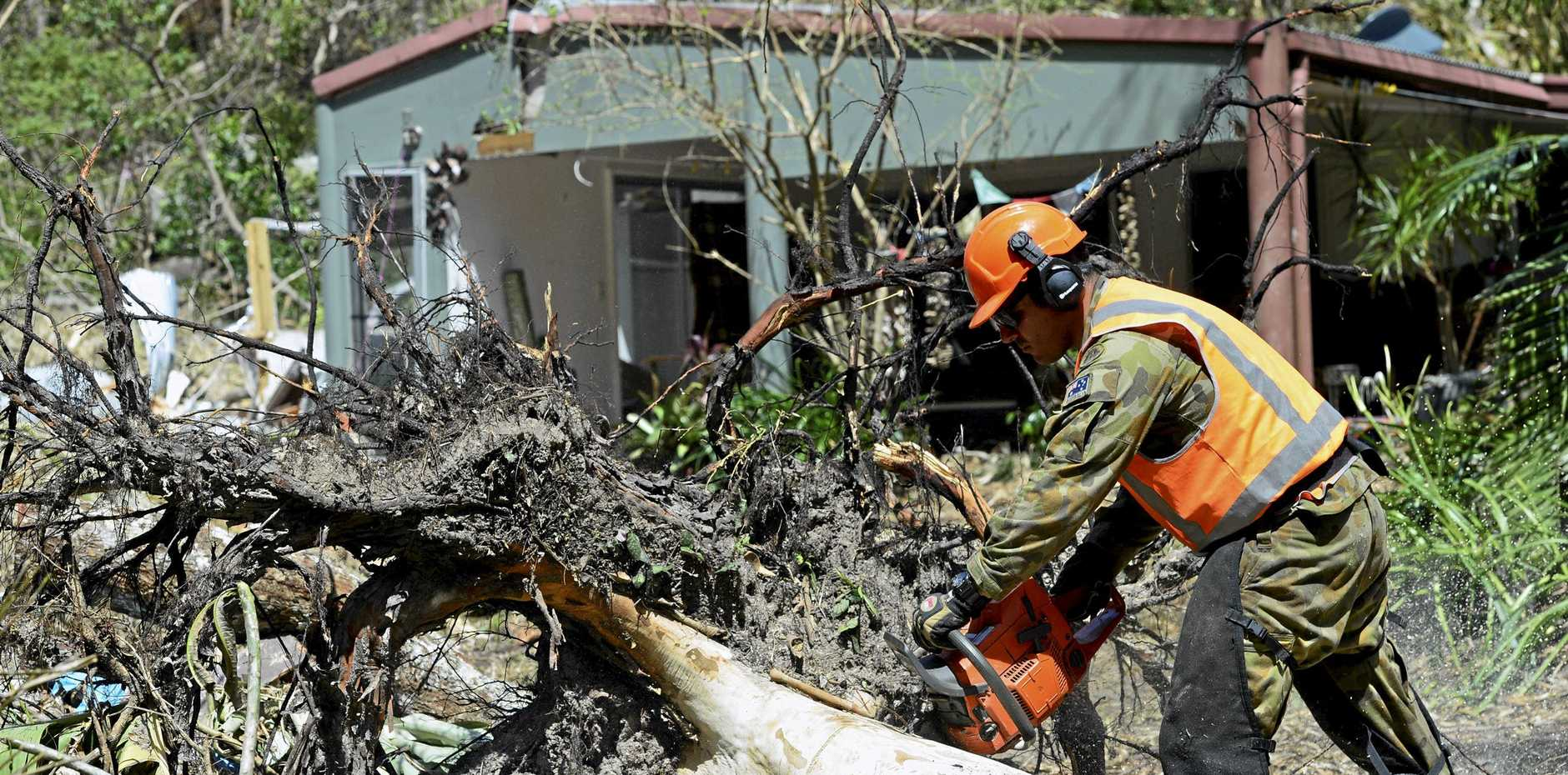 AFTERMATH: The Australian Defence Force member helping John Hughes, at Airlie Beach home, by cutting logs that fell on his house Cyclone Debbie.