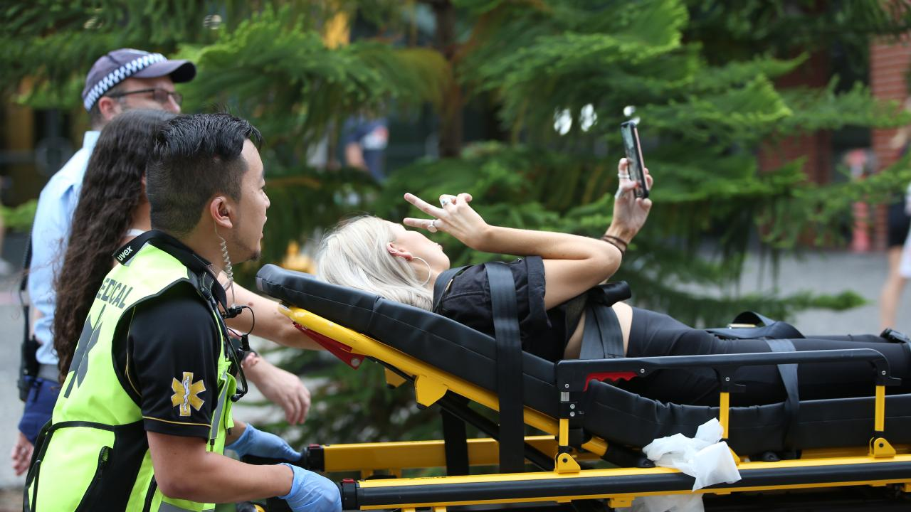 A girl takes a selfie as she is taken away on a stretcher outside the Rolling Loud Festival. Picture: Damian Shaw