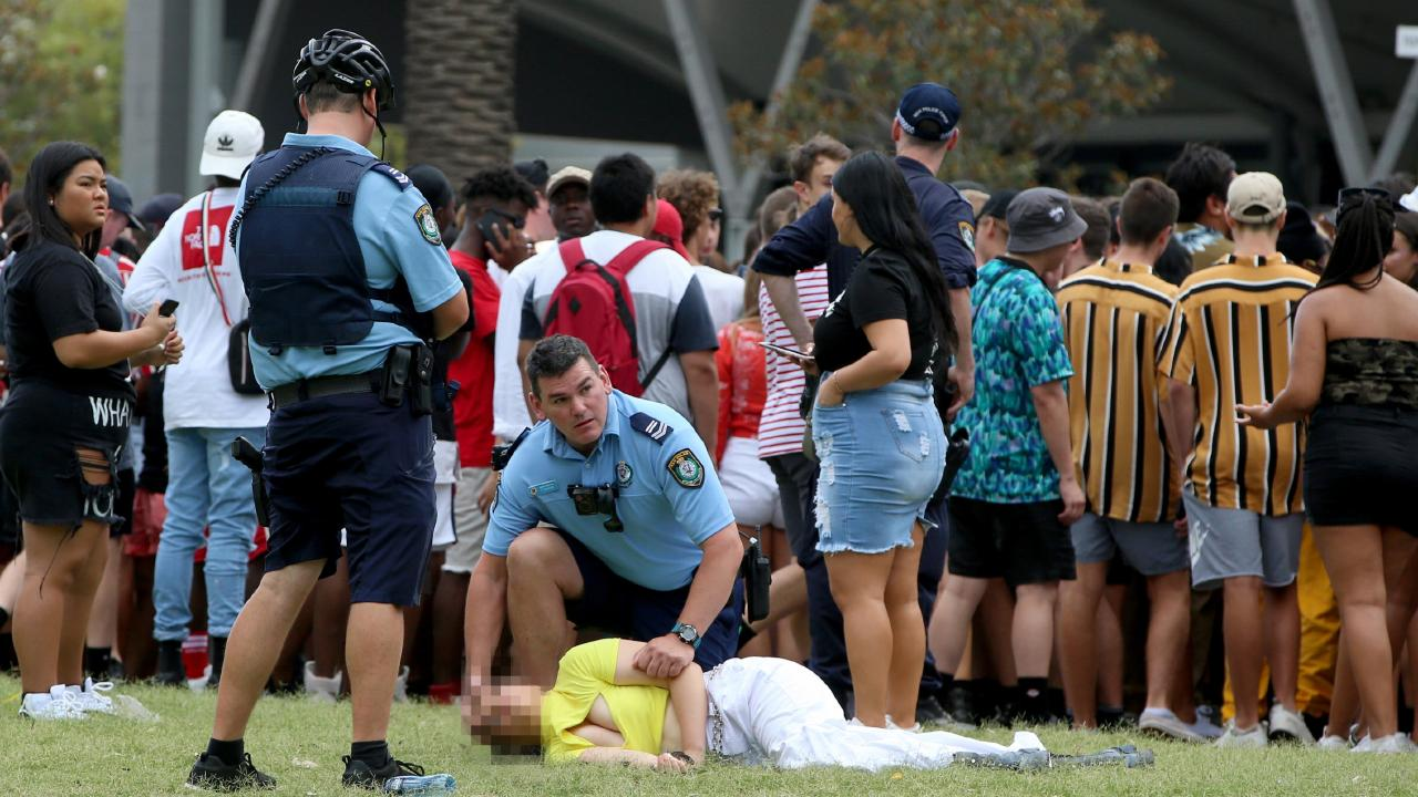 Two police officers helping a girl passed out on the ground. Picture: Damian Shaw