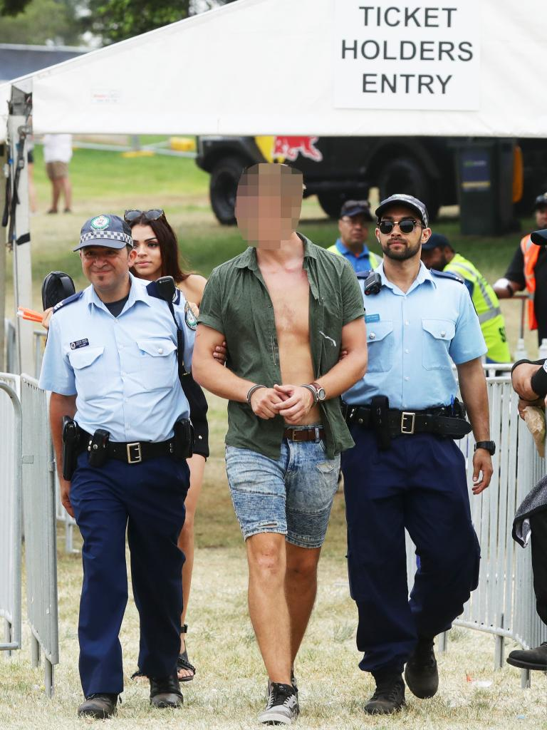 A man is led away by police from the Electric Gardens music festival in Centennial Park. Picture: Matrix