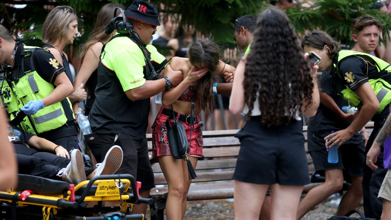 A young girl is helped by paramedics as another reveller (left) is stretchered away. Picture: Damian Shaw