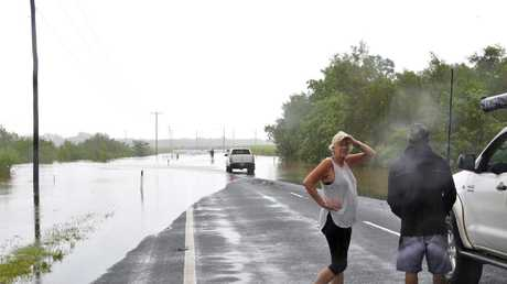 Motorists contemplate driving through flood waters on Dunne Road in Smithfield. Picture: PETER CARRUTHERS