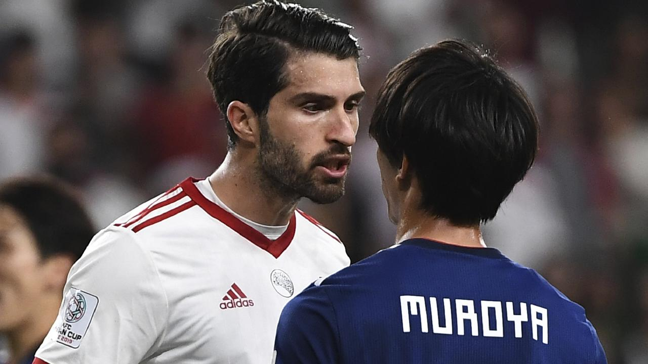 Iran's forward Karim Ansarifard argues with Japan's defender Sei Muroya.