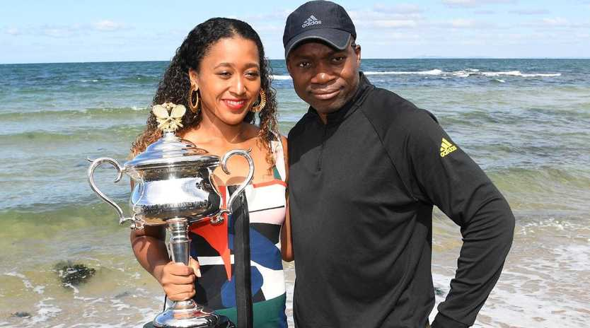 Naomi Osaka poses with her father Leonard Francois and the Daphne Akhurst Memorial Cup at Brighton Beach. AAP Image/Julian Smith