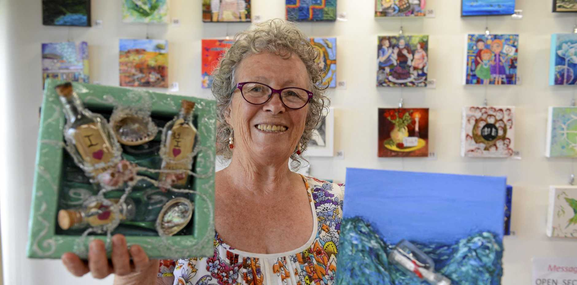 Lower Clarence Arts and Crafts member and 8x8 co-ordinator Suz Monin with two of the many exhibits that were entered into last year's competition. Entries are now open for this year's event.