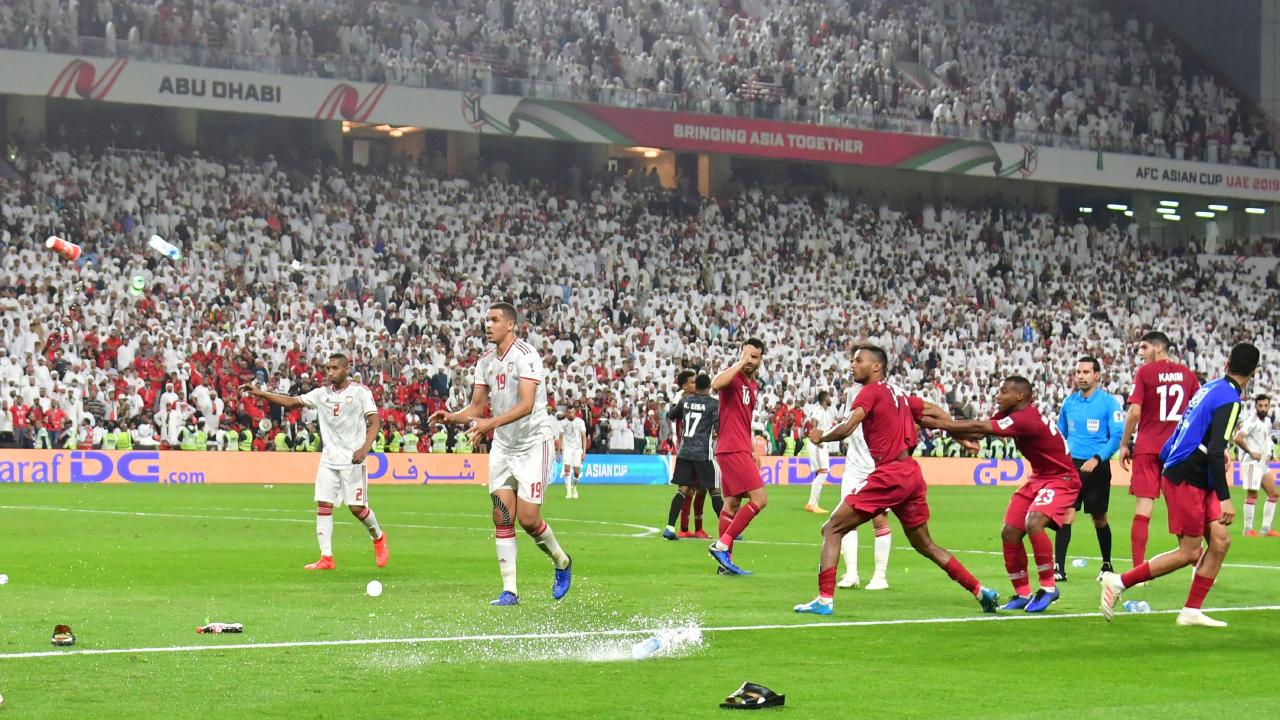 TOPSHOT - Fans throw bottles and flip-flops at the pitch during the 2019 AFC Asian Cup semi-final football match between Qatar and UAE at the Mohammed Bin Zayed Stadium in Abu Dhabi on January 29, 2019. (Photo by Giuseppe CACACE / AFP)