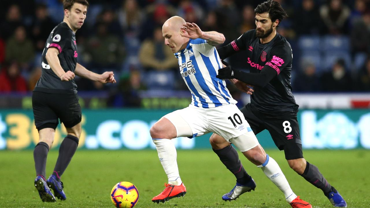 Aaron Mooy of Huddersfield Town is challenged by Andre Gomes of Everton