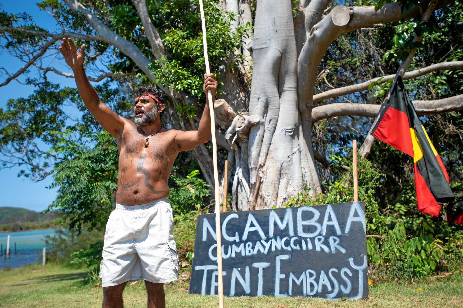 Buagin waves to a passer-by at the front of the Gumbaynggirr Tent Embassy.