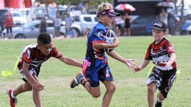 SWIFT: Aiden Tom from Tweed Coast Giants U10 boys team sliding between Coomera Chief defenders at the Queensland Oztag Age Championships on the Sunshine Coast.