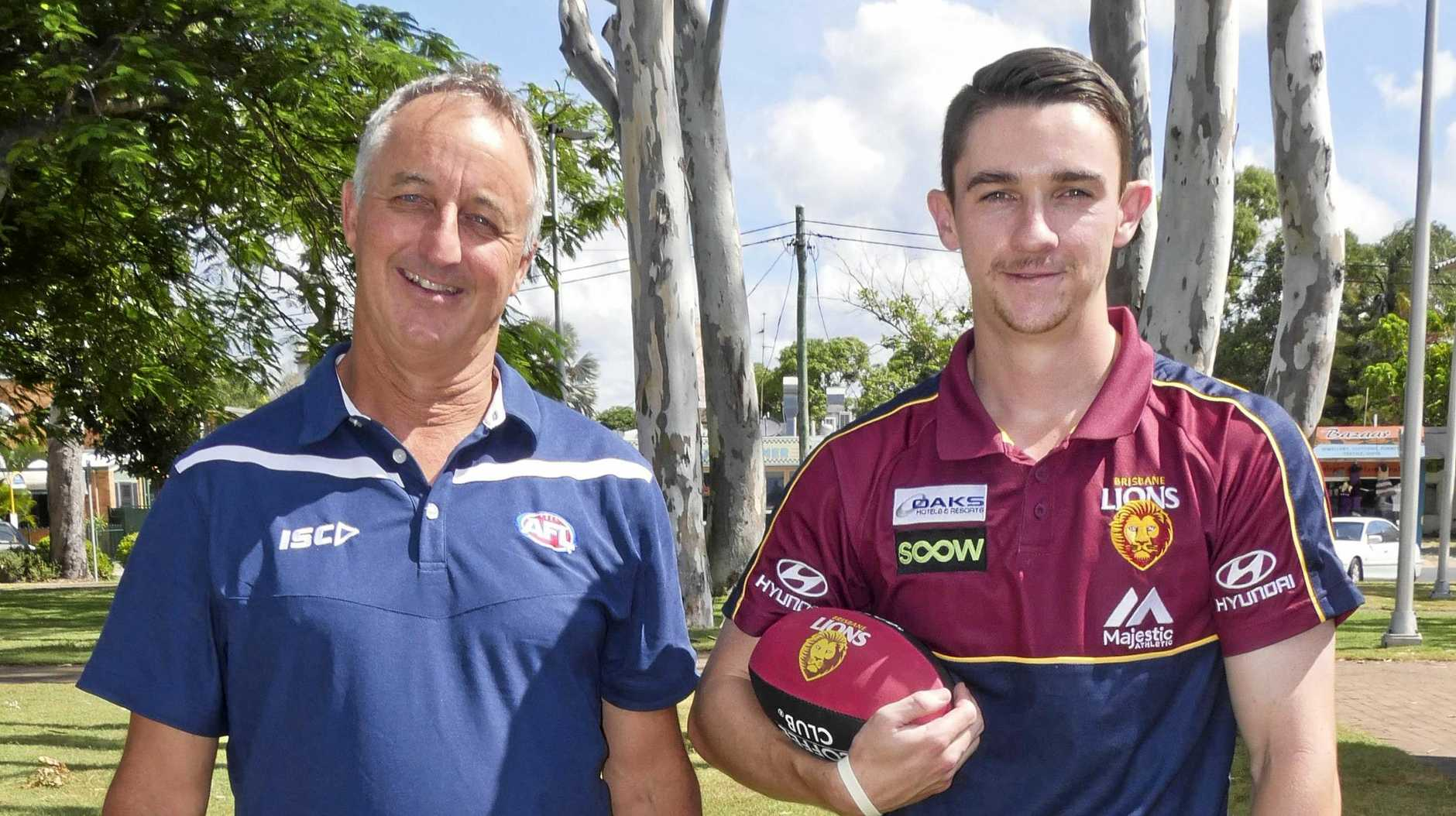 AFL Queensland's Sunshine Coast and Wide Bay regional manager Paul Tresise with Fraser Coast development coordinator Kieron Hyndman practicing their handballs in Torquay ahead of five Brisbane Lions players visiting the region.