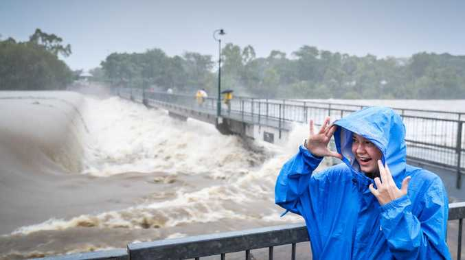 Jessica Mackail checks out the Ross River powering over Aplins Weir. Picture: Michael Chambers