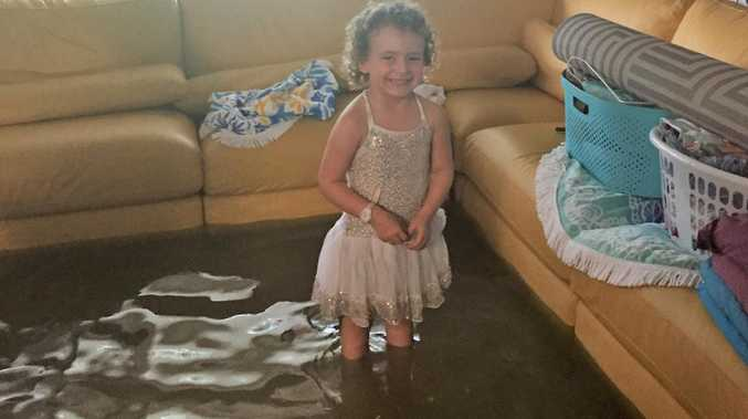 Flash flooding at Deeragun, Townsville February 2, 2019. Four-year-old Bailee Hanran stands in her lounge room. Photo: Tess Ikonomou