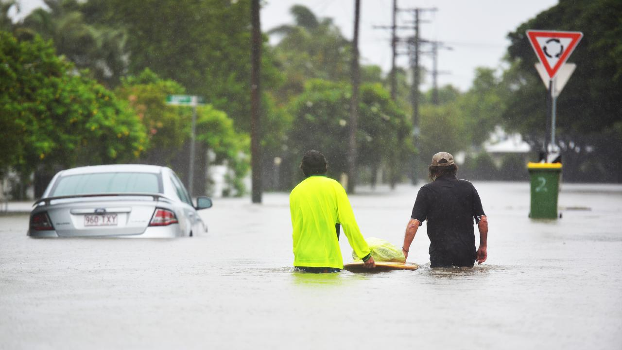 Residents of Rosslea being evacuated as Townsville continues to flood from heavy monsoonal rain. Locals push belongings on a surfboard. Picture: Alix Sweeney