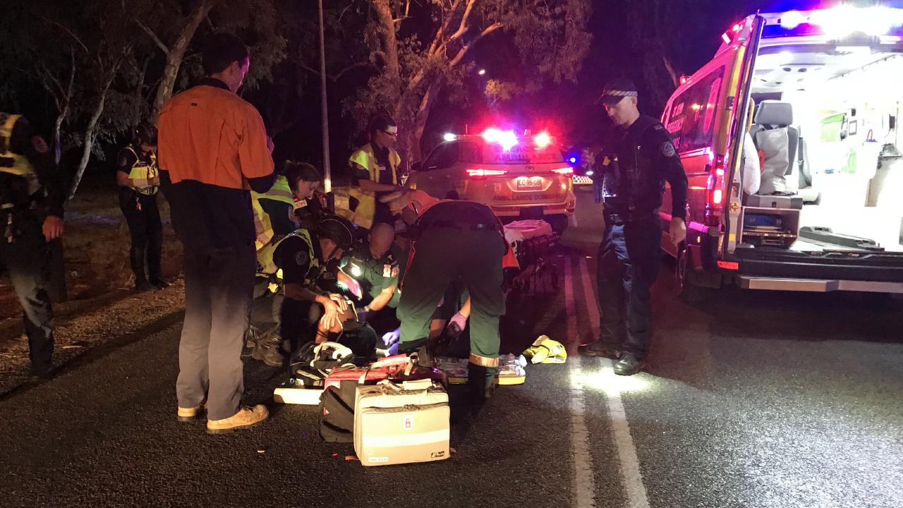 Paramedics and emergency services personnel work to stabilise on Ida* in the left hand lane of Leichhardt Terrace. Picture: Kristin Shorten