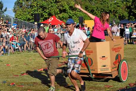 Mike O'Connell and Ray Stecca pull Kerri Stecca to victory in the Chinchilla Melon Festival Chariot Race, which saw teams construct and haul their melon-laden vehicles over the line for cash prizes.     Photo Alasdair Young / Chinchilla News
