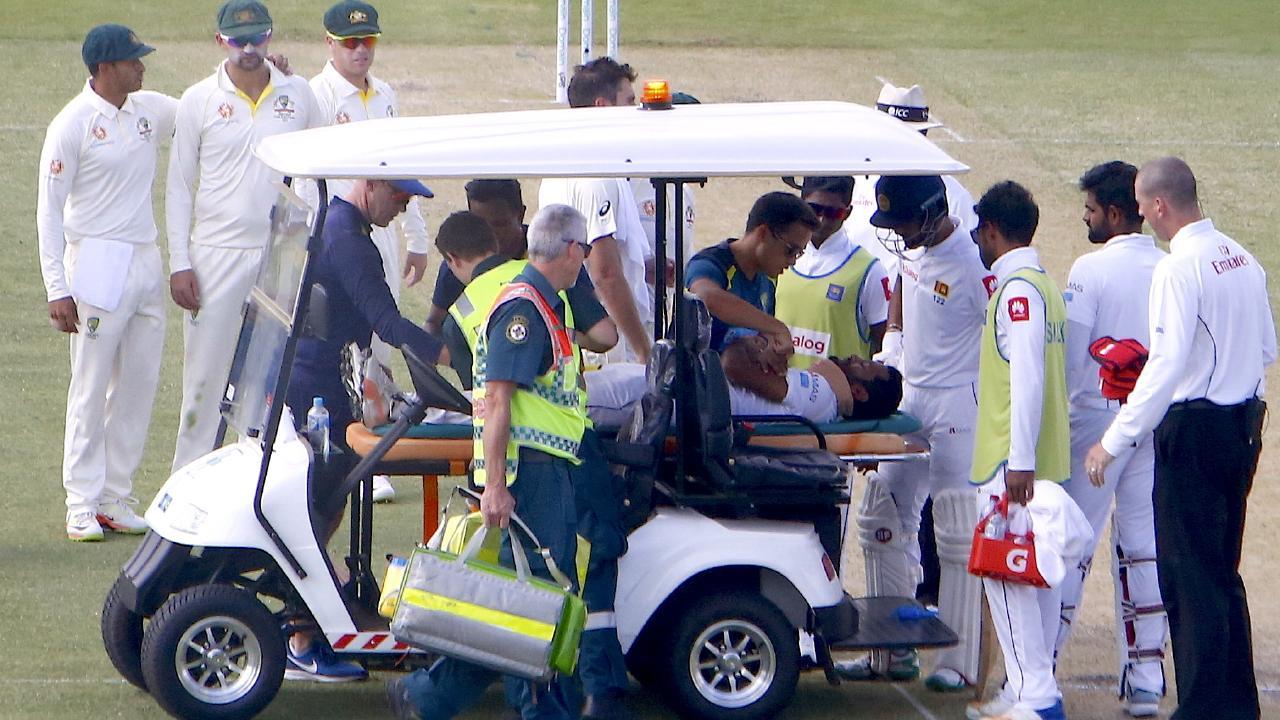 Members of the Australian team watch as medical staff assist Sri Lanka's Dimuth Karunaratne. AAP Image/David Gray