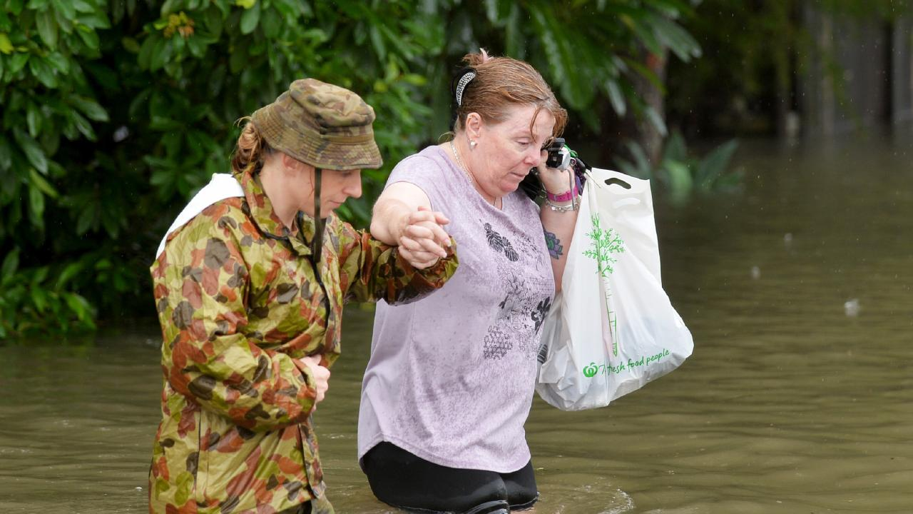 CPT Stacey Brown helps Robin Webb from her house after she returned to see the devastation. Picture: Alix Sweeney