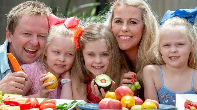 Scott and Fiona Annett with their kids, Sophie (8) and 6 year old twins Tilly (in blue) and Jessie with healthy produce. Picture: Jay Town