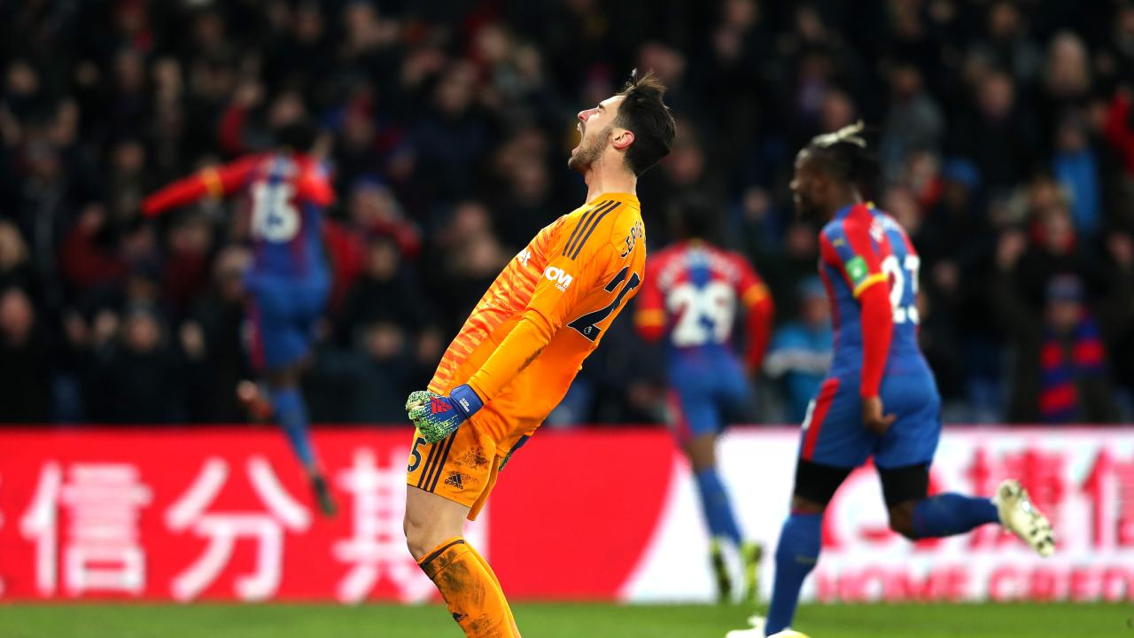 Sergio Rico of Fulham reacts as Jeffrey Schlupp of Crystal Palace (obscure) celebrates after scoring his team's second goal