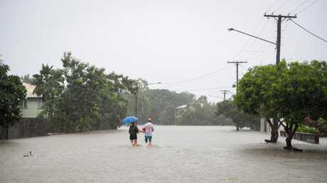 A couple head home down a flooded street in Townsville. Photo: Michael Chambers.
