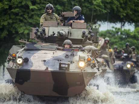 Australian soldiers drive through flood waters in Hermit Park, Townsville. Picture: Glenn Hunt/The Australian