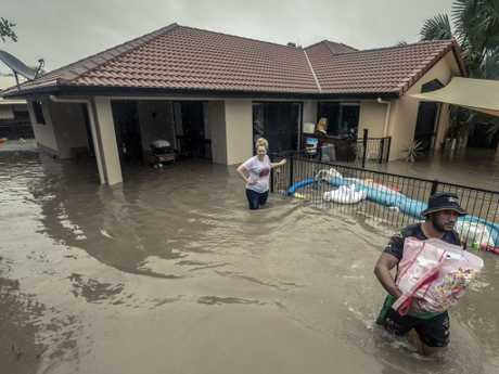 NRL player Kalifa Faifai Loa helps Danielle Josey and Lyndon Josey remove valuable belongings from their home in Idalia, Townsville. Picture: Glenn Hunt/The Australian