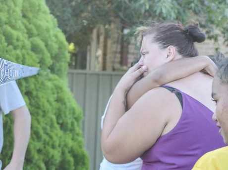 A woman, believed to be the child's mother, is comforted at the scene.