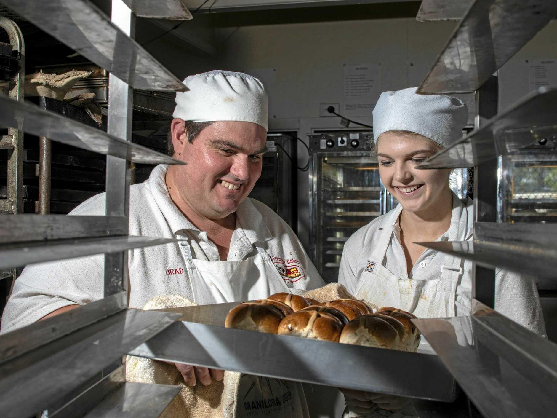 Old Fernvale Bakery pastry chef Brad Gordon and second year apprentice Chelsea Roberts inspect one of the first batches of hot cross buns for the bakery's annual fundraiser.